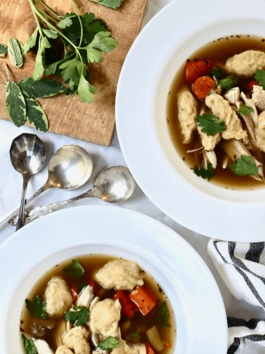 Bowls of clear chicken broth with cooked carrots, shredded chicken, sourdough dumplings, and fresh herbs.