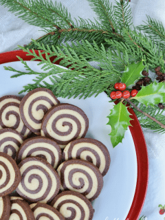 A festive, holly garnished plate showing the tight spiral of these black and white pinwheel cookies.
