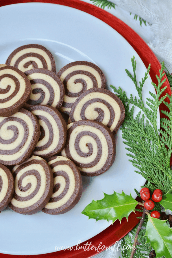 A festive, holly-garnished plate showing the tight spiral of these black and white pinwheel cookies.