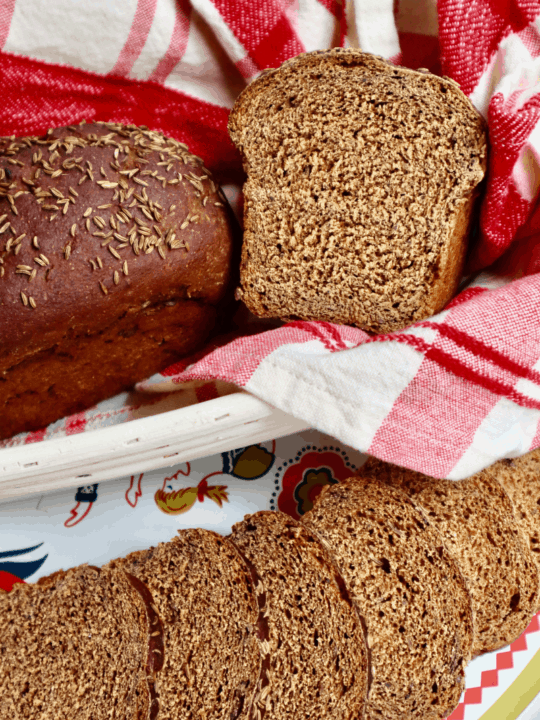 Close up of a sourdough rye loaf cut to reveal the perfect, even, dark brown crumb.