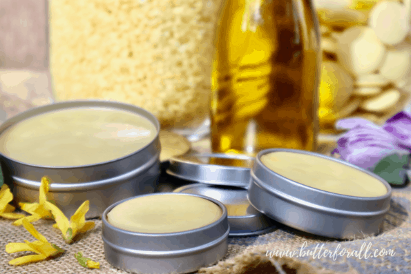 Different sized tins with solid golden salve made from beeswax, cocoa butter, and olive oil.