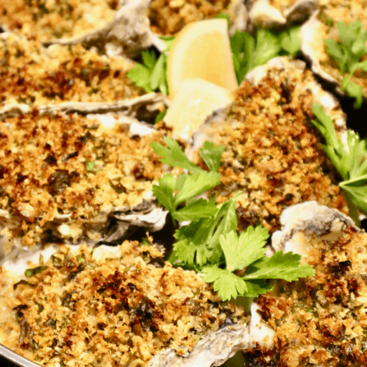 A baking pan displaying freshly baked oysters with sourdough breadcrumb topping.