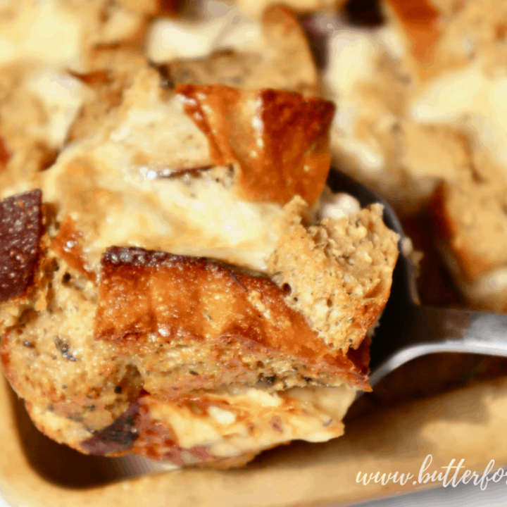 Scooping hot sourdough bread pudding from the pan.